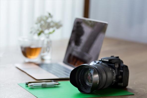 Kamera mit Laptop im Hintergrund in den Farben Gold und Grün - für ihren Firmenauftritt