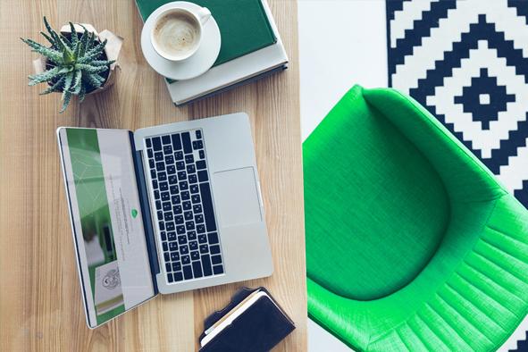 Leerer Stuh in Grün vor einem Schreibtisch mit Laptop und offener WebSite - steht sinnbildlich für WebDesign